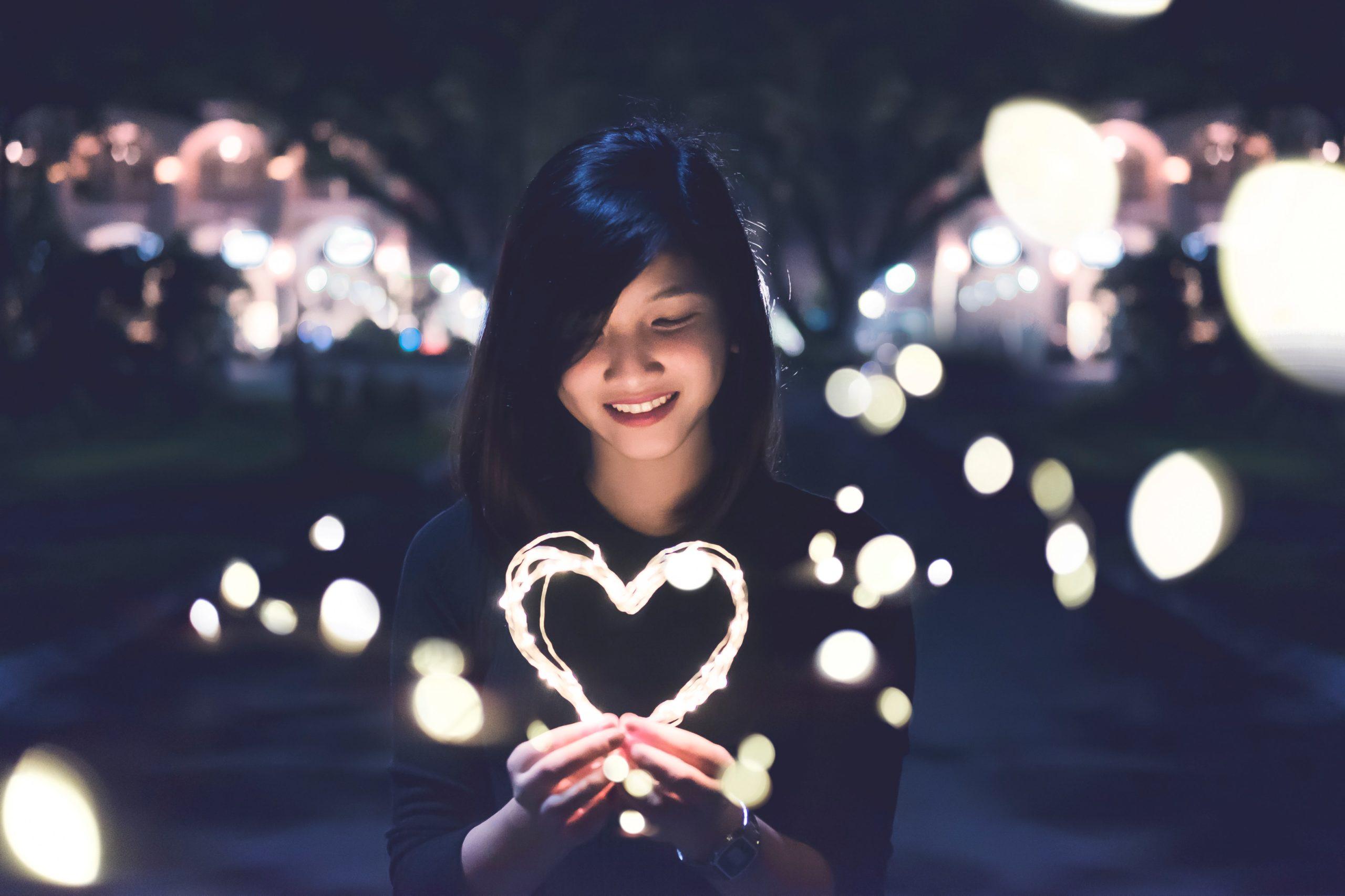Femeie cu o inima de lumina in mana.